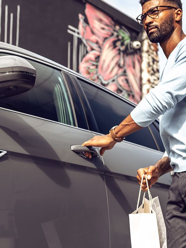 Man goes to open the driver's door of a VW Atlas Cross Sport with a shopping bag in hand.