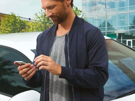 A fashionable man in a lightweight jacket stands in the parking lot of a business district looking at his phone happily.