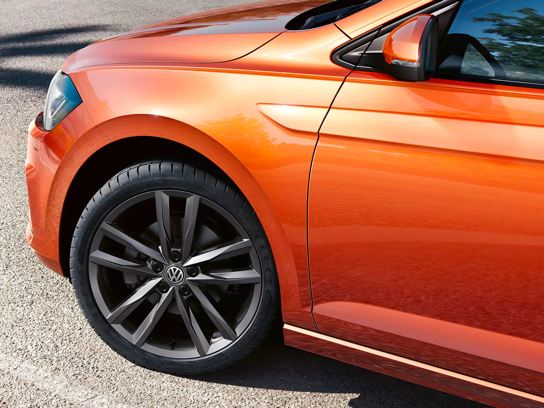 An angled front driver's side silhouette showcases a habanero orange Volkswagen Jetta.