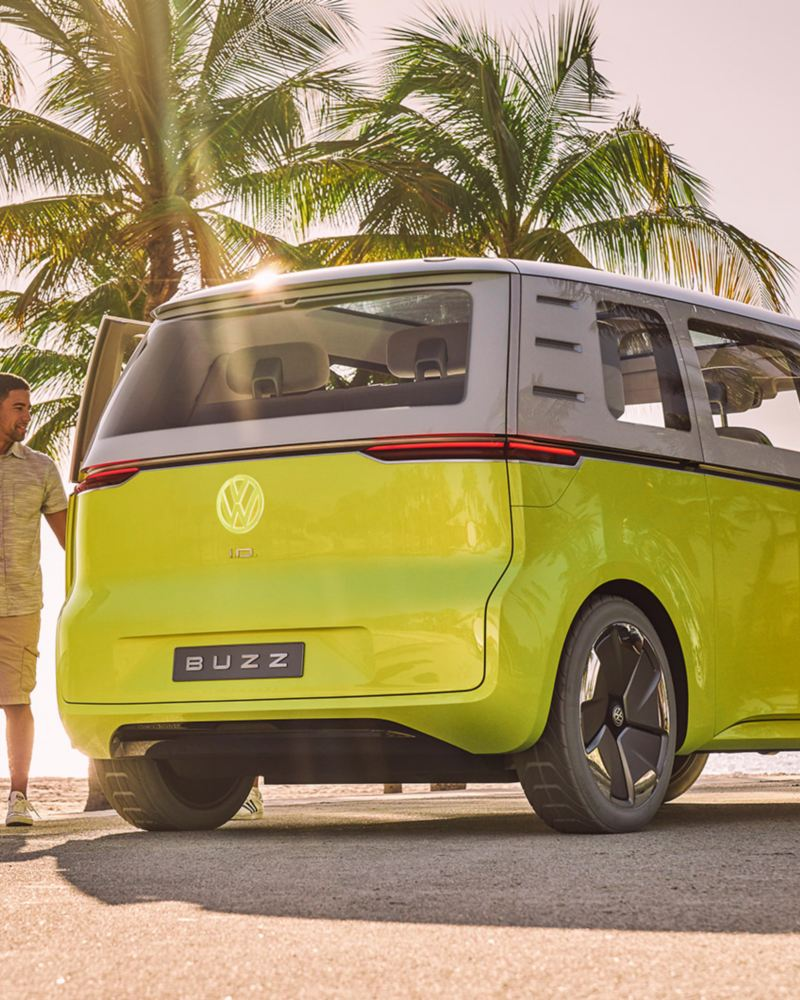 Three people standing outside an ID.BUZZ concept vehicle parked on a sandy beach.