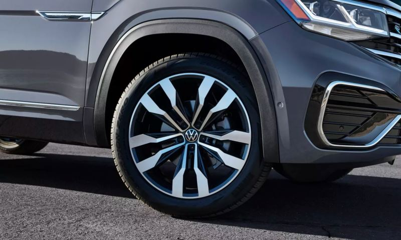 A sharply lit angle of a platinum gray metallic Volkswagen Atlas Cross Sport showcases its passenger's side R-Line wheel.
