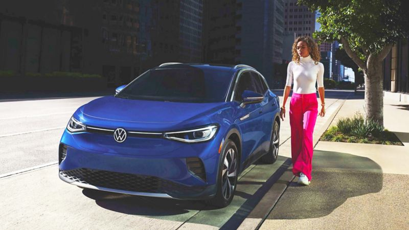 Woman in hot pink pants, sunglasses, and cream turtleneck approaches dusk blue metallic Volkswagen ID.4 parked off-street.