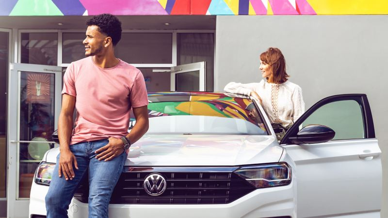 Millennial man and woman casually lean and pose on a pure white Volkswagen Tiguan outside of dealership.