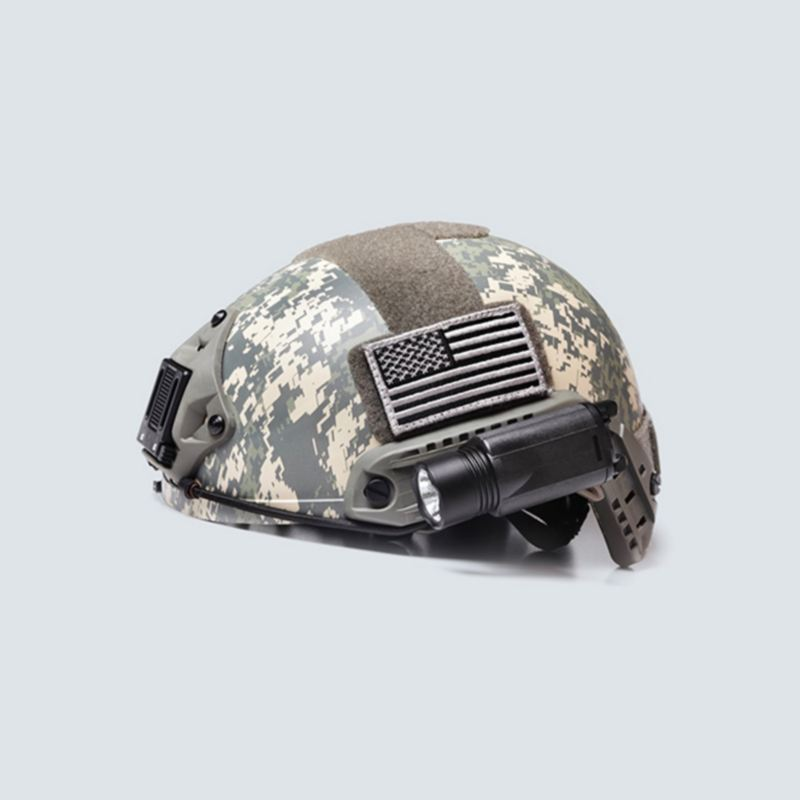 A camo helmet with a flashlight and flag patch