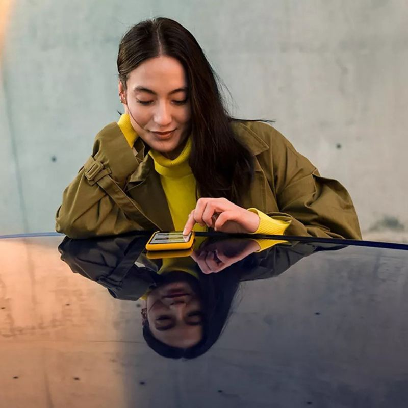 A stylishly dressed woman gazes at her smartphone.
