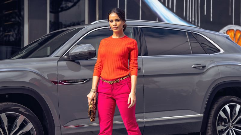 A brightly-dressed woman with a leopard clutch struts past a platinum gray metallic Volkswagen Atlas Cross Sport.
