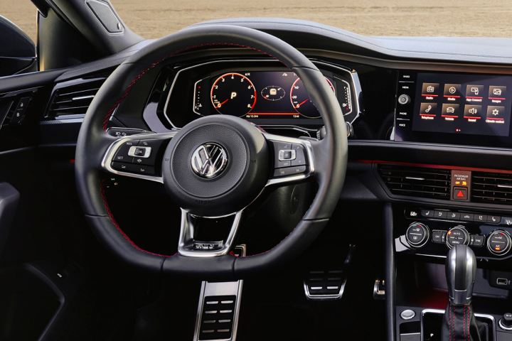 The VW Golf GTI digital cockpit, media touch screen, and famous flat-bottom steering wheel with honeycomb detail.