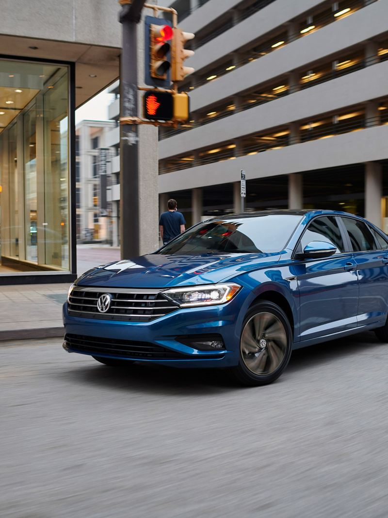 A tourmaline blue metallic Volkswagen Passat R-Line makes a right turn in the heart of a downtown street.