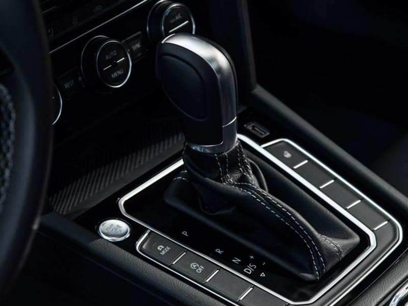 Keyless push-start button and brushed silver trim accompany stitched black leather gear shift of Volkswagen vehicle.