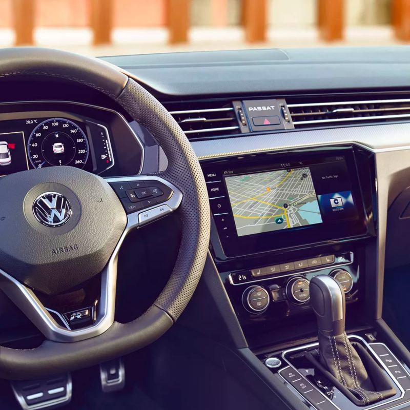 The luxurious Volkswagen Passat interior, showcasing the digital cockpit, navigation touchscreen, and leather gear shift.