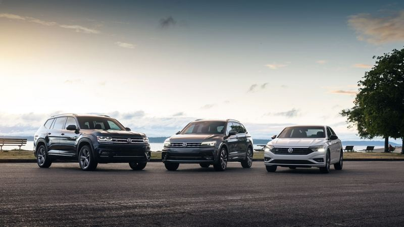 The sun sets on an Atlas Cross Sport, Tiguan, and Jetta R-Line, parked and posed on road downstage from a picturesque lake.