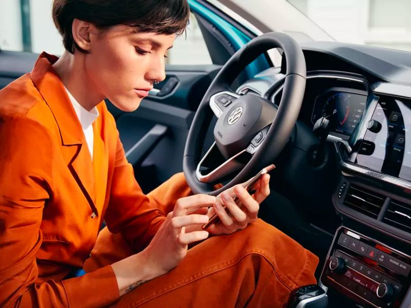 A chic young woman in a casual burnt orange pantsuit sits in the driver's seat of a parked vehicle scrolling through phone.