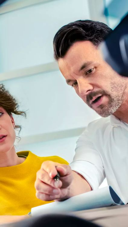 A young woman in a mustard yellow sweater sits with sales manager to review paperwork.