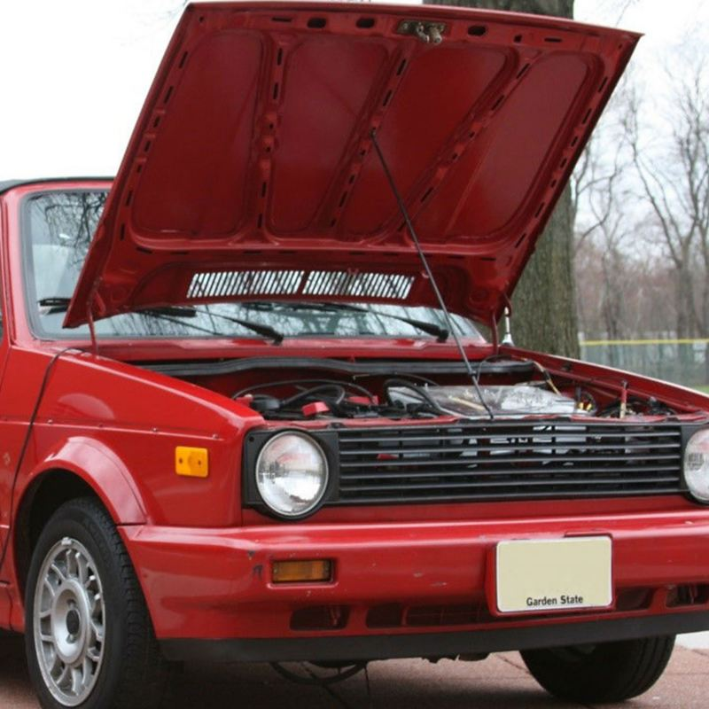 A red 1990 Volkswagen Cabriolet that has been converted from gas to electric is parked with its hood open.