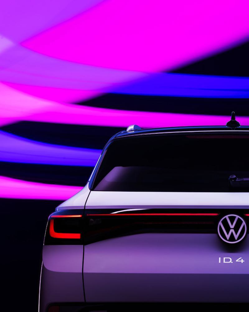 The brake lights of a VW ID.4 EV shown in Glacier White metallic are illuminated in the dark. Strokes of purple, pink and blue light add texture to the otherwise dark background.