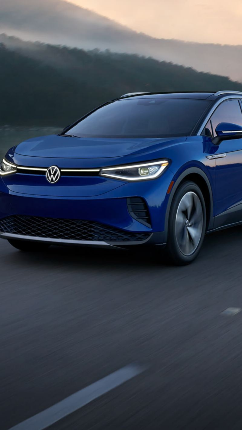 A VW ID.4 EV in Metallic Dusk Blue drives on a two-lane highway with mountains in the background.