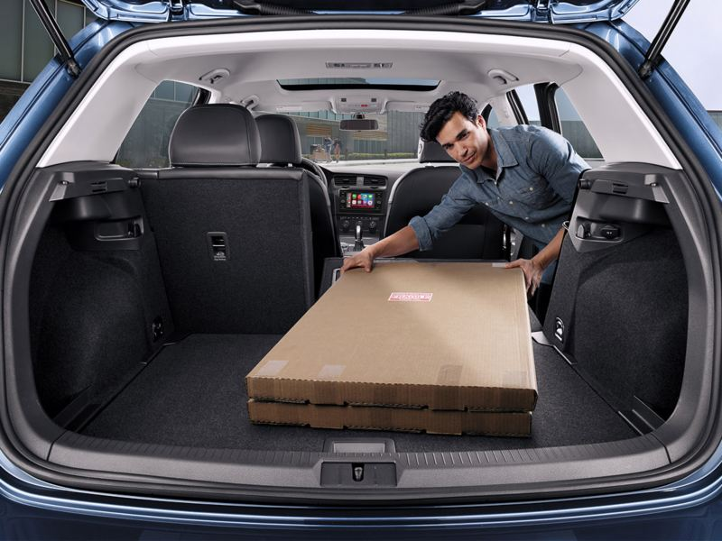 A man places a package in his Volkswagen Golf using the 60/40-split folding rear seats seen from the back of the vehicle.