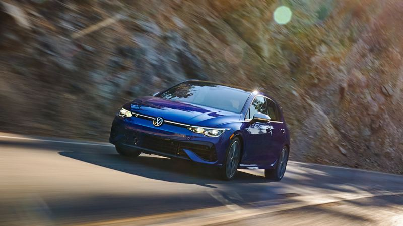 A Pure White Golf and a Silk Blue Metallic Golf parked in front of a mural