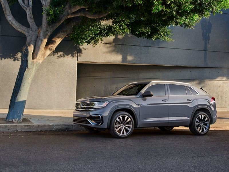 Side view of the Atlas Cross Sport in Pure Gray parked alongside a building.