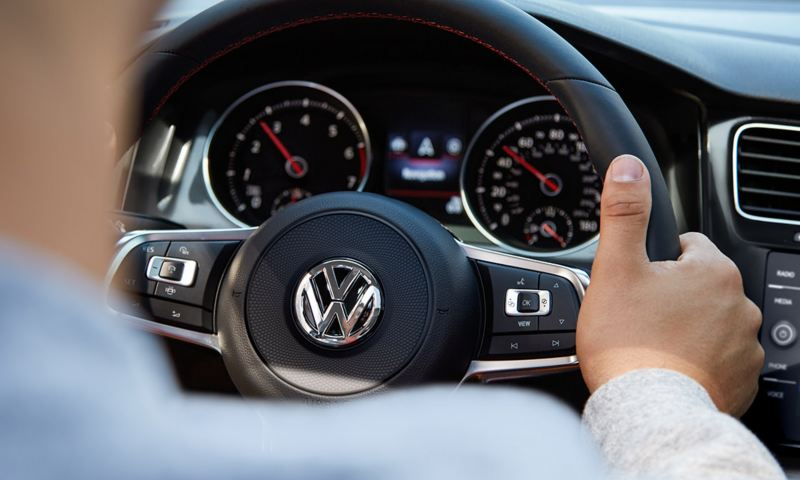 Over the shoulder shot of a male holding the steering wheel in the Golf GTI.