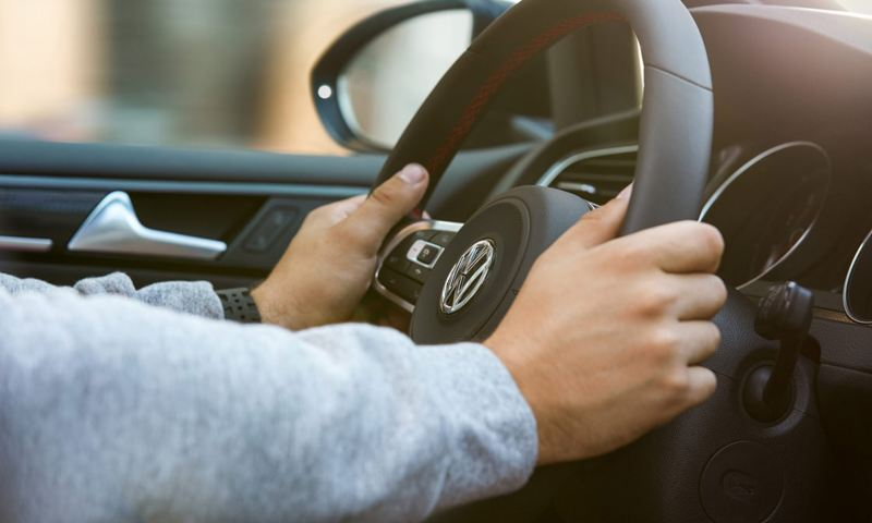 A male driver's hands comfortably placed on the steering wheel